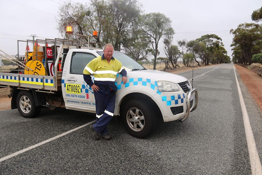 A man in high vis leans on his white ute parked across a rural stretch of road, with road closed signs in the back.