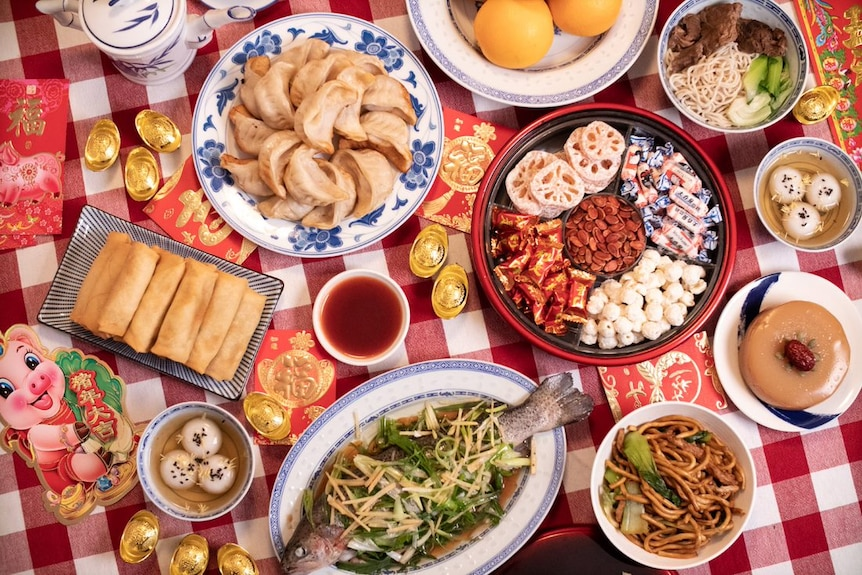 8 lucky Lunar New Year foods including dumplings, spring rolls, oranges, whole fish, year cake and sweet rice dumplings.