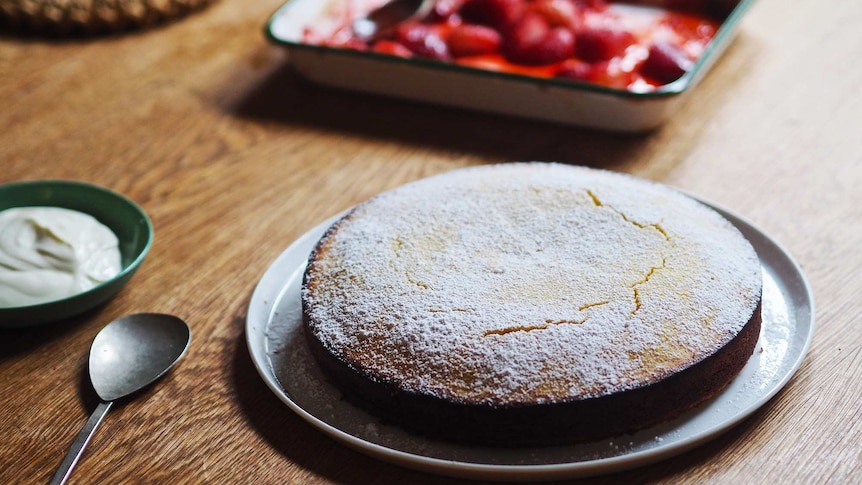 Lemon almond cake dusted with icing sugar served with yoghurt and roasted strawberries, an easy cake for afternoon tea.