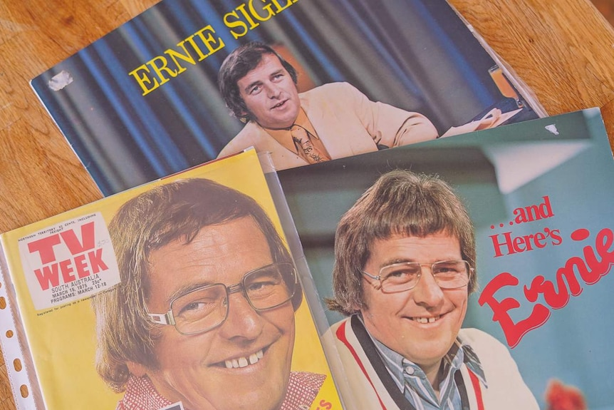 An old magazine and two records with Ernie Sigley's face and name on their covers sit on a wooden table.