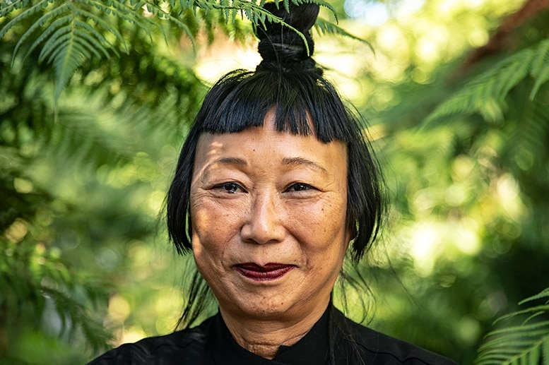 A woman with black hair tied up in top knot and Mao collar style jacket smiles in lush green outdoor area surrounded by ferns.