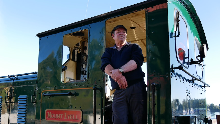 A train engine driver standing in doorway of green carriage.