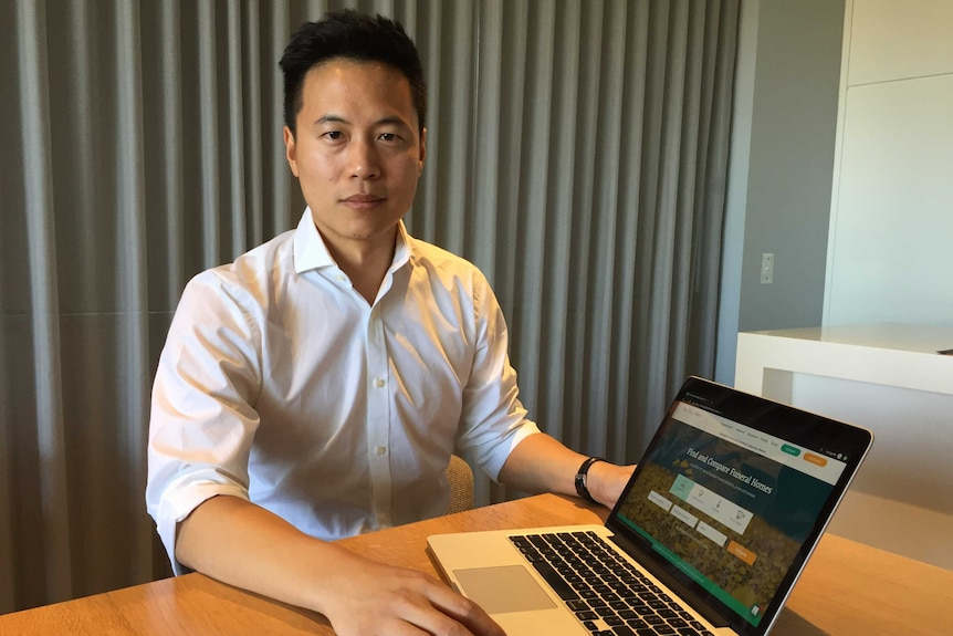 Colin Wong show his funeral cost comparison website on a laptop computer
