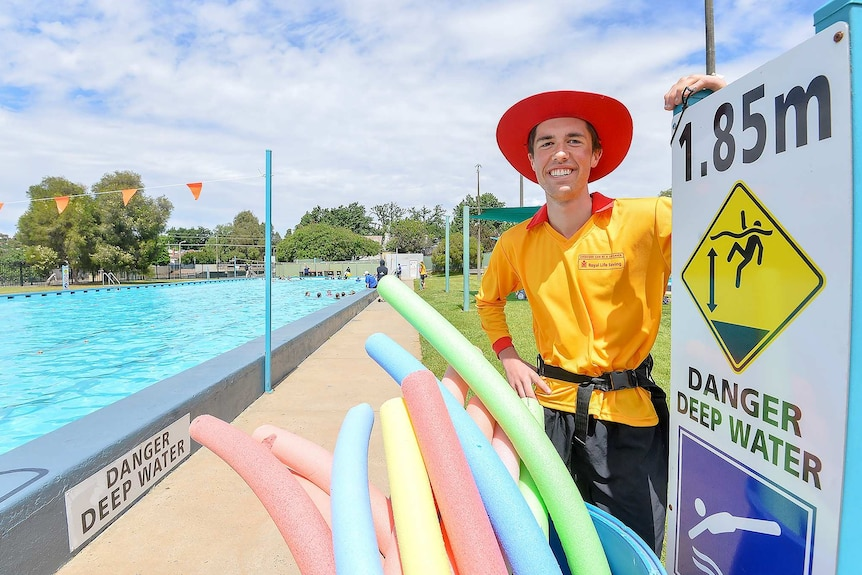 A smiling man of indeterminate age, wearing lifesaver gear and standing in front of a pool.