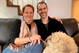 A woman and a man wearing glasses sitting with a dog on their laps.