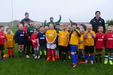 A large group of smiling children in bright football uniforms standing on a soggy field on a grey day.