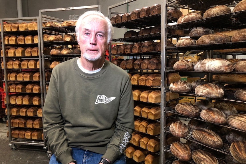 man in front of racks of bread in a bakery setting