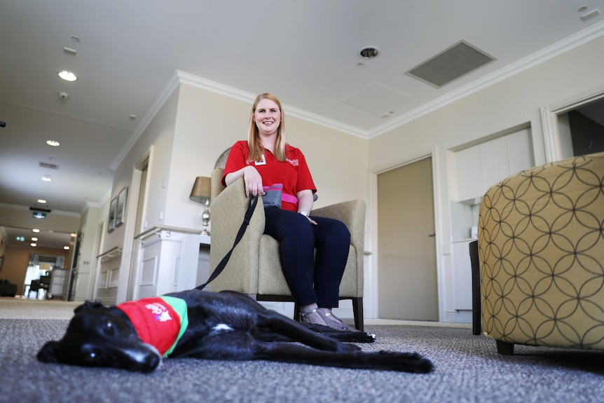 Alana Wade sits in a chair as therapy dog Tiffany lies on the ground.