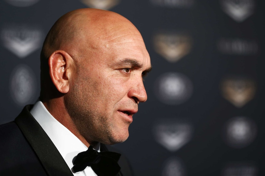 A former rugby league player dressed in a tuxedo, pictured in profile.