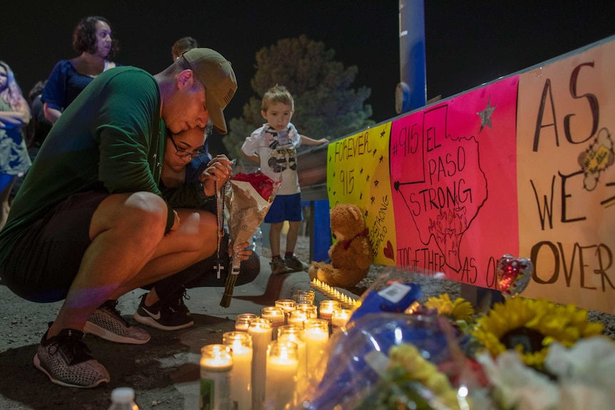 A men bends over in front of signs, candles and toys for victims