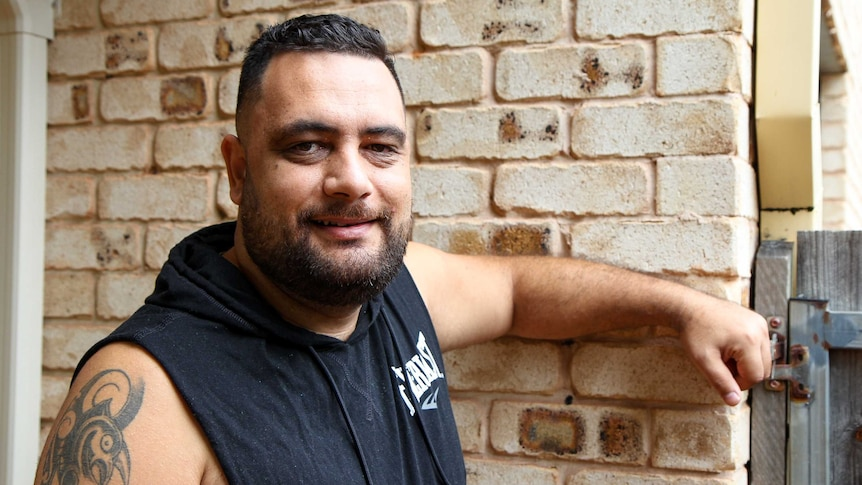 A New Zealand man with a tattoo on his arm leans against a brick wall.