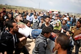 An injured man is carried by severall men at the site of the clashes near gaza
