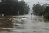 A submerged car on a flooded road.