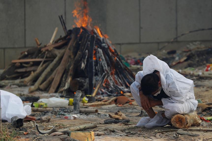 A man crouches down and hangs his head as a fire burns behind him.