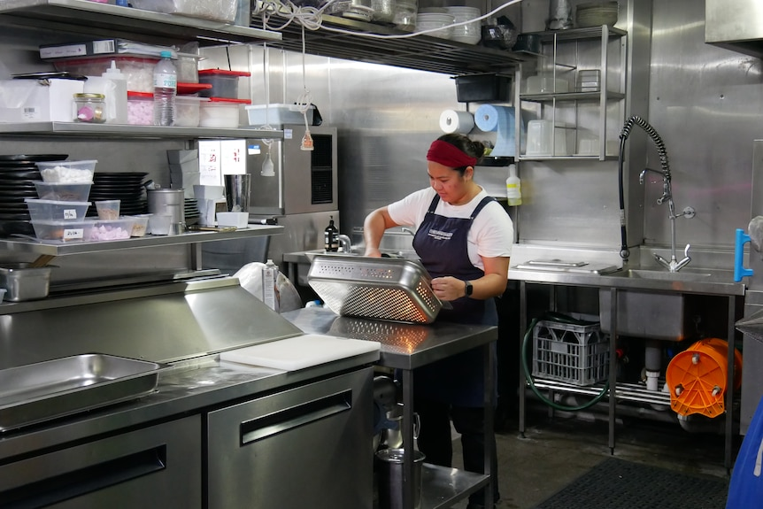 A woman works in an industrial kitchen