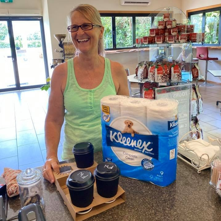 Smiling woman stands at a cafe counter with a nine-pack of Kleenex toilet paper and three takeaway coffees.