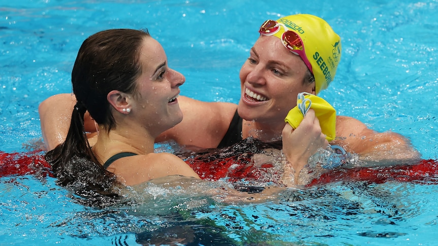 A brunette woman swimming next to another woman wearing a yellow swimming camp