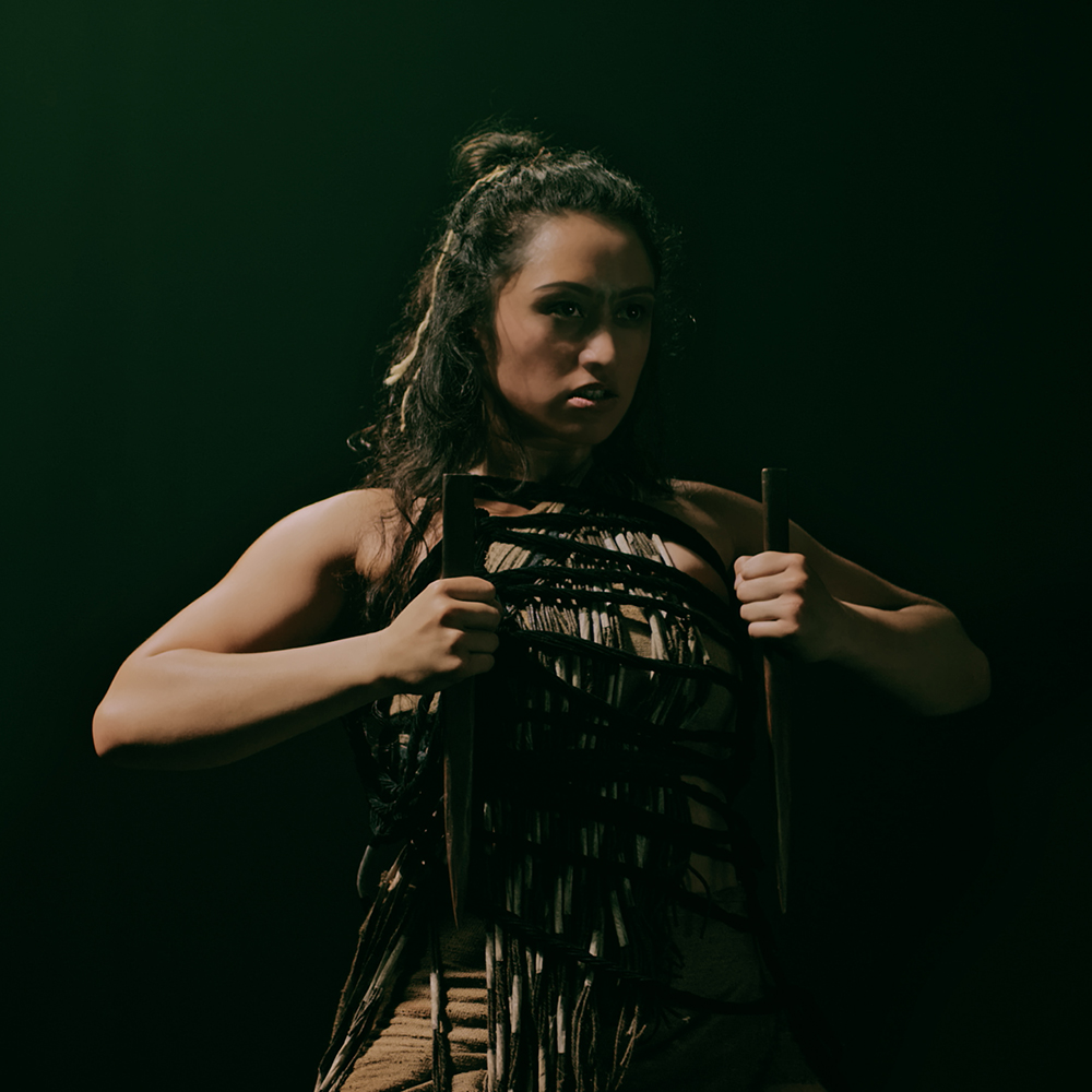 A woman with half hair up, half in bun, wears traditional Māori attire and holds two staff weapons in each hand close to chest.