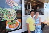 A man and a woman standing in front of a food van