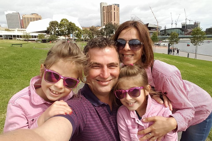 Flaviu Lazar takes a selfie of himself with his partner and two daughters on the banks of Adelaide's Torrens River.