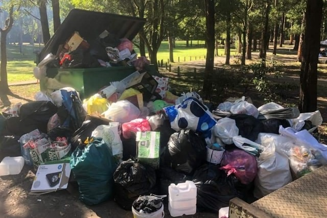 Piles of rubbish around a full skip at a campsite in south-west Victoria
