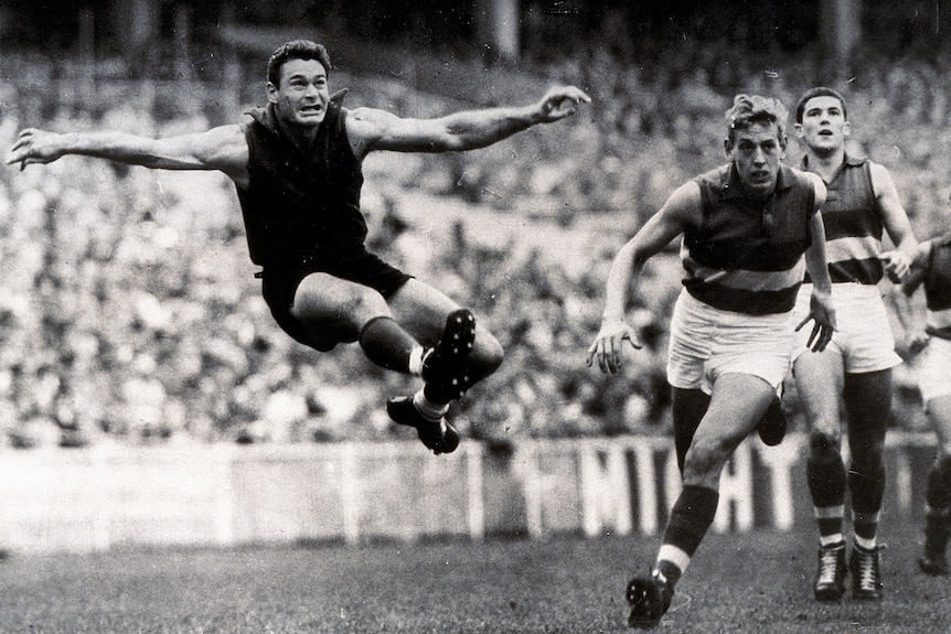 Ron Barassi is airborne as he kicks the ball with both arms stretched wide