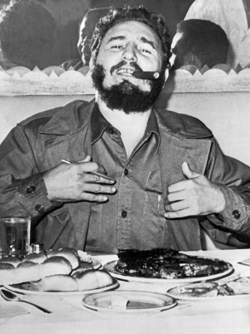 Black and white photo of Fidel Castro eating a steak during a press conference in 1960.