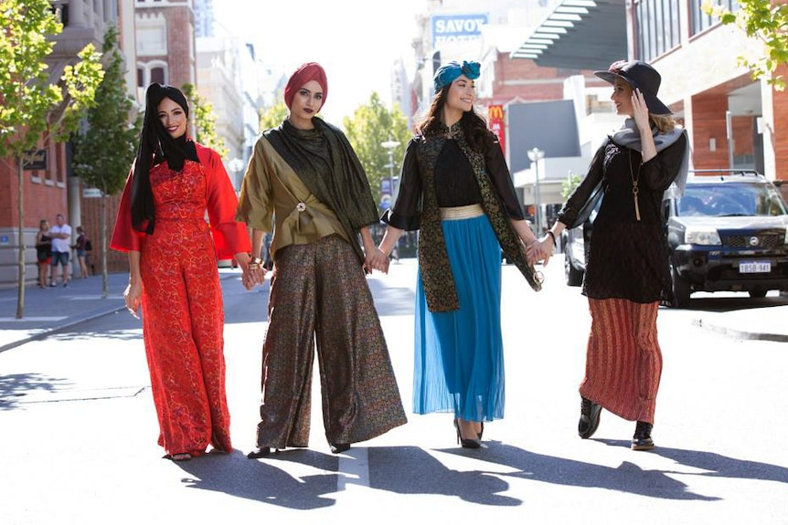 Four modest fashion models stand in the street holding hands.