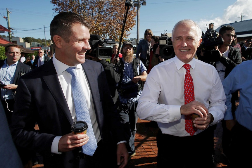 Mike Baird and Malcolm Turnbull walk down a street in Merimbula surrounded by media.