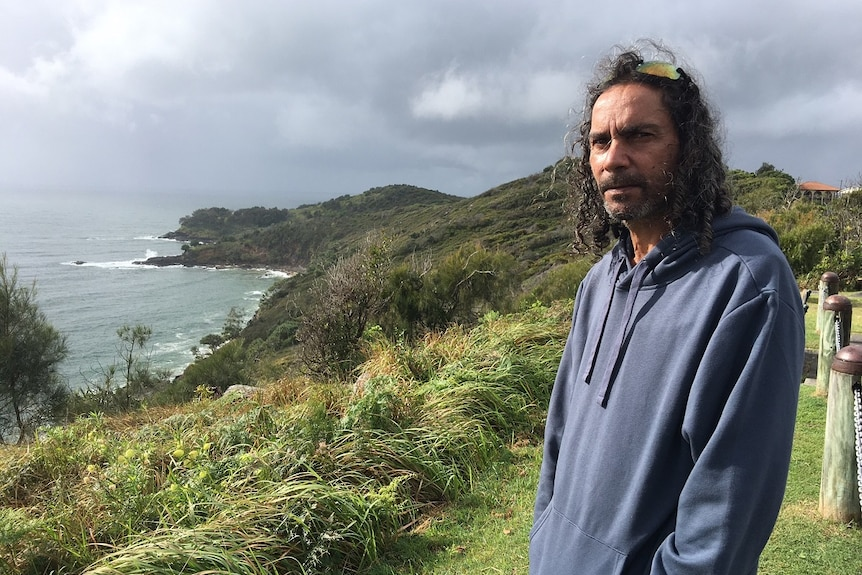 A man stands in front of a headland