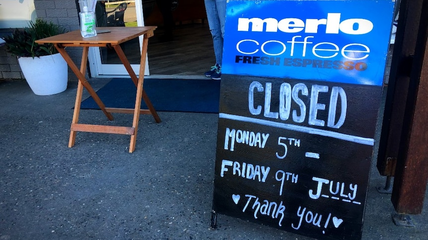 A sign in front of a cafe that says 'closed'