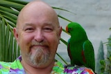 A smiling bald man with a goatee wears a bright shirt and a parrot on his shoulder.