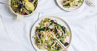A bowl of pad thai salad with tongs served onto two dinner plates with chopsticks, illustrating our simple recipe.