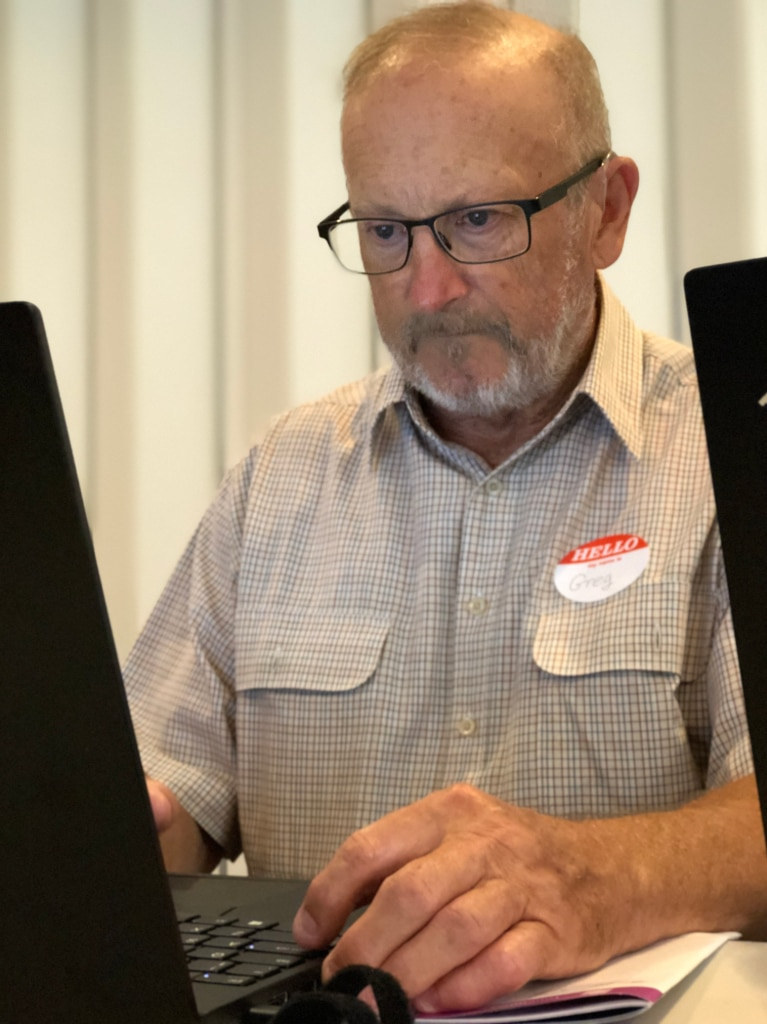 Older man sitting in front of a computer screen looking determined.