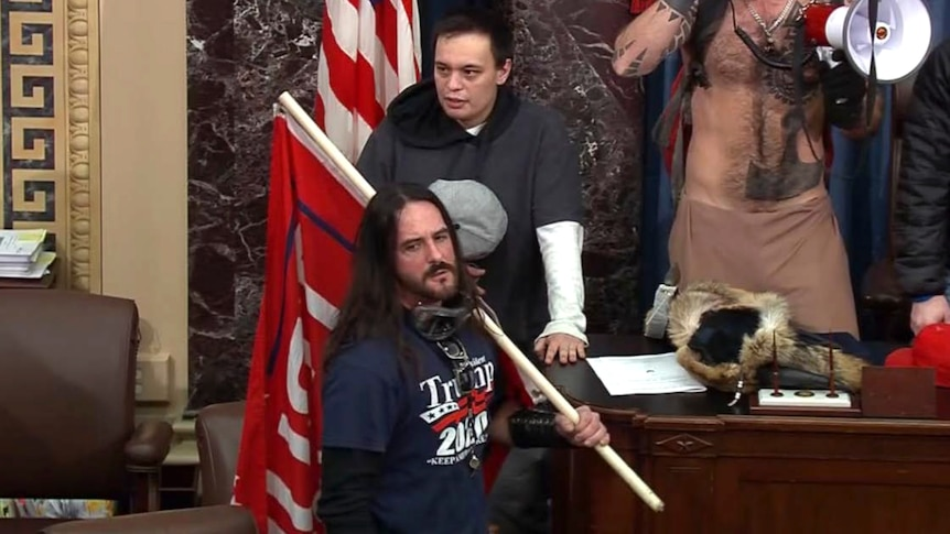 A man stands in the Us Senate with a flag and wearing a Trump t shirt