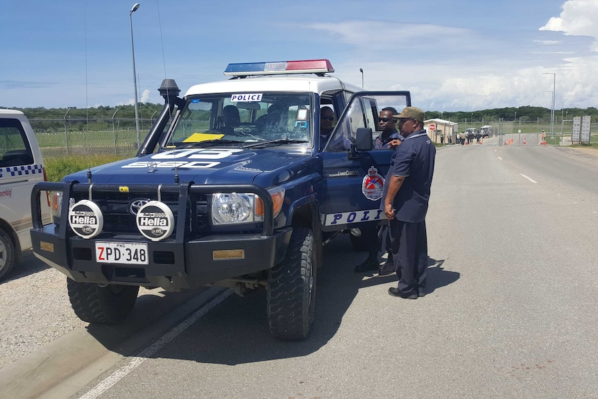 PNG police mill around a police car near an LNG plant near Port Moresby.