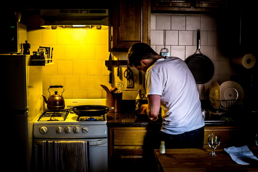 A man cooking in a small kitchen.