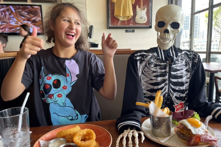 A teenage girl with brown hair sits next to a skeleton in a restaurant with her thumbs up.