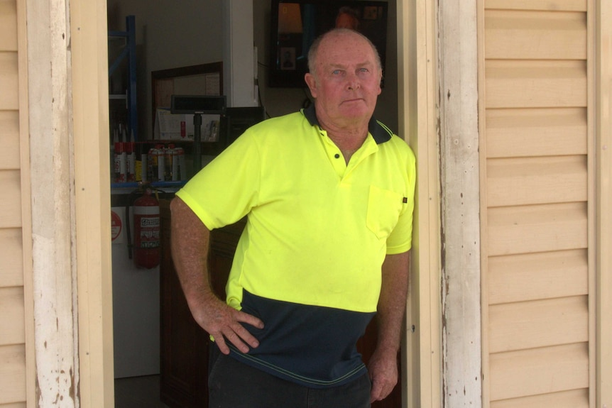 A man in a yellow high visibility shirt leans in a doorway looking at the camera.