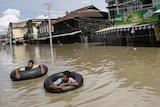 Men wade along a flooded street at Kalay township at Sagaing division