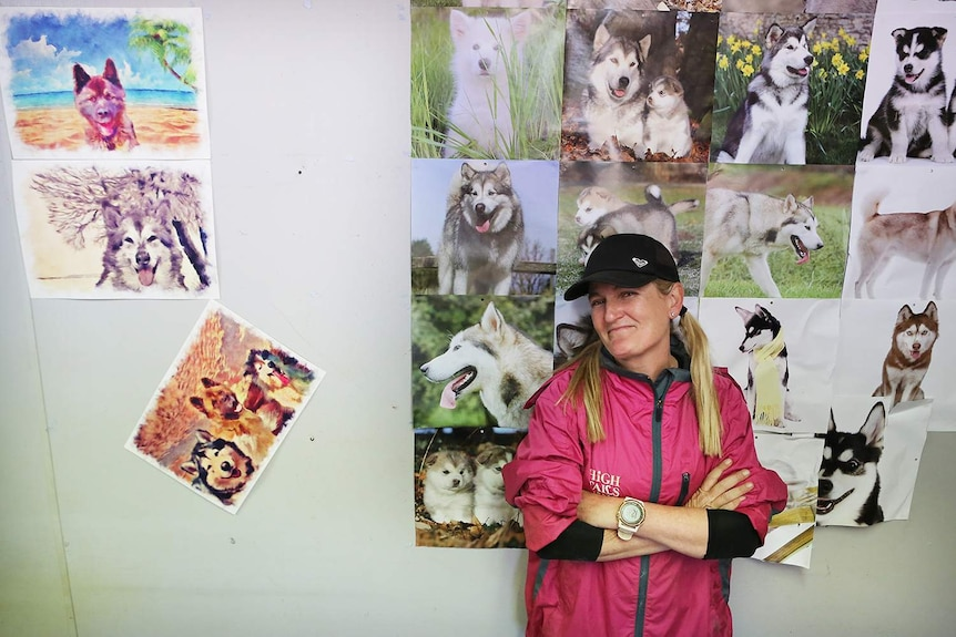 Janelle Wyatt leaning up against a wall of dog pictures.