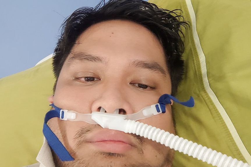 A person with brown hair lies on a yellow pillow with a tube in his nose.