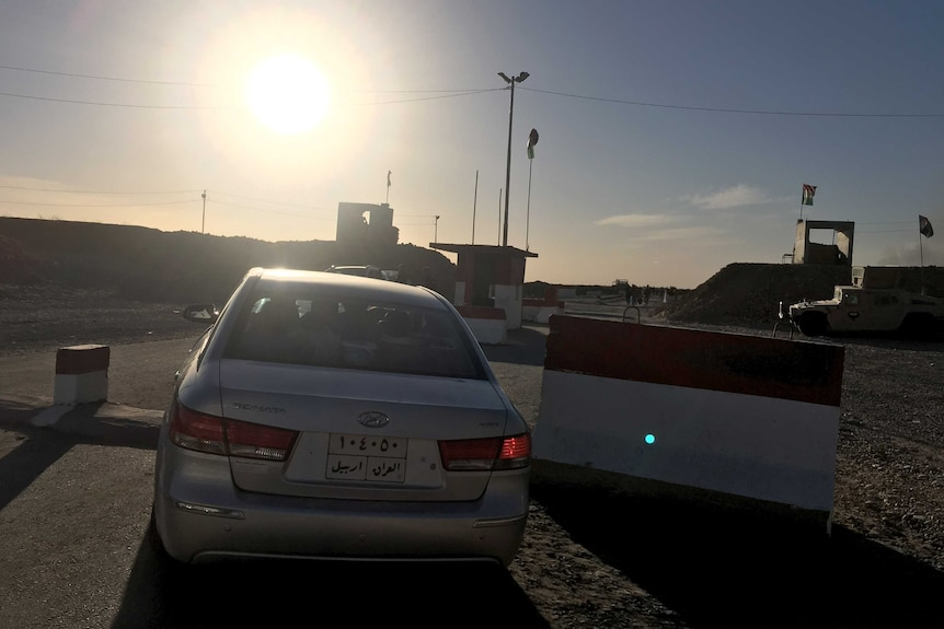 An Iraqi family's car passes the checkpoint in Makhmour, Iraq, on the way back to their village.