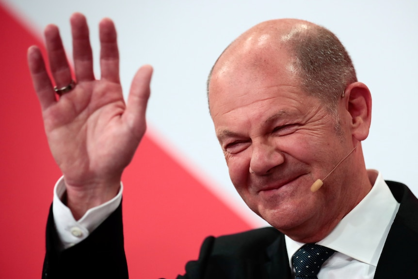 German politician Olaf Scholz waves while smiling.