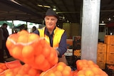 Man in orange vest throws large bag of oranges on a table. He wears a hat and a smile