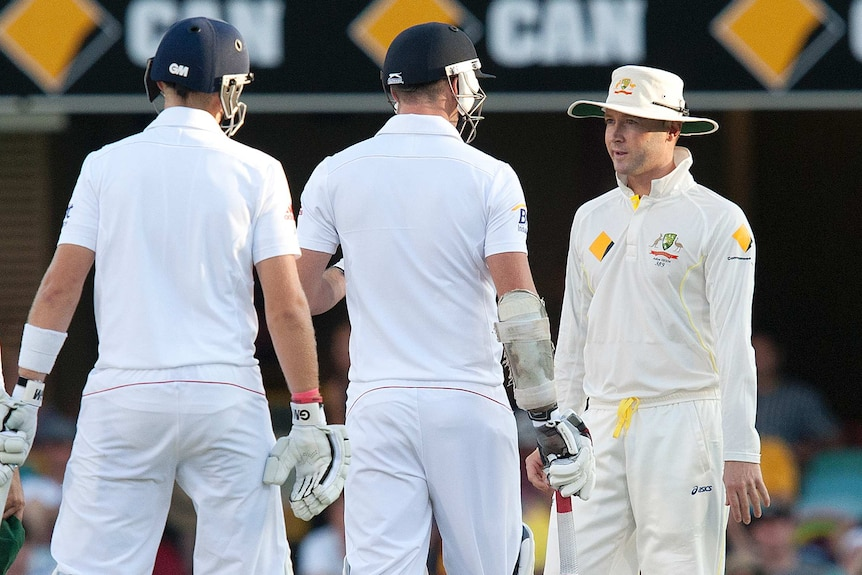 Michael Clarke speaks to James Anderson while another England batsman looks on during play in a Test match.