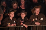 Three children wear veteran's medals, faces lit by candle light.
