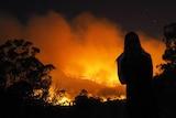Silhouette of woman watching bushfire at night near Agnes Water.