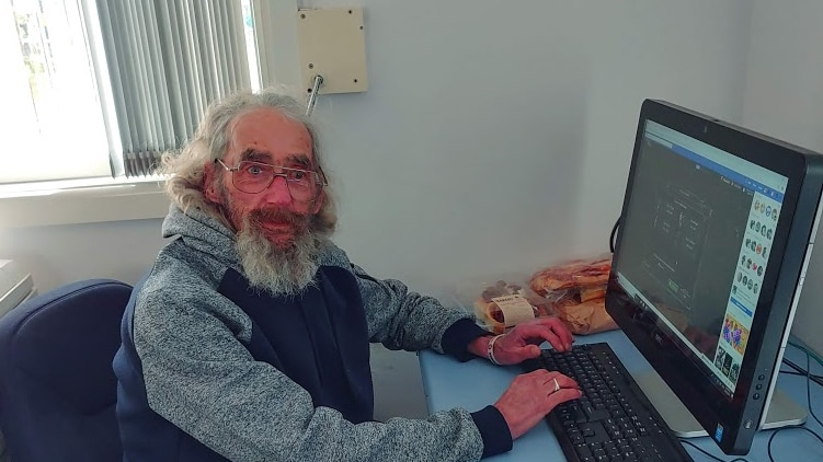 Wally Douglass sits at computer