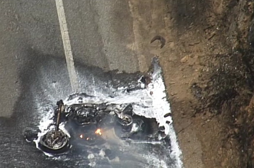 A burnt motorbike laying on the ground with water and foam doused over it.